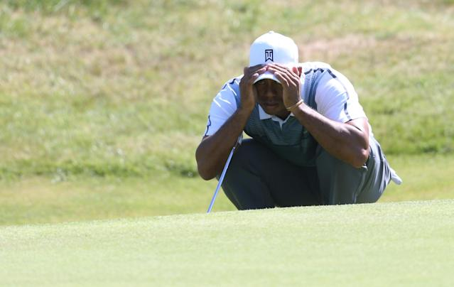 Tiger Woods of the US looks at his putt on the 9th green during the first day of the British Open Golf championship at the Royal Liverpool golf club, Hoylake, England, Thursday July 17, 2014. (AP Photo/Peter Morrison)