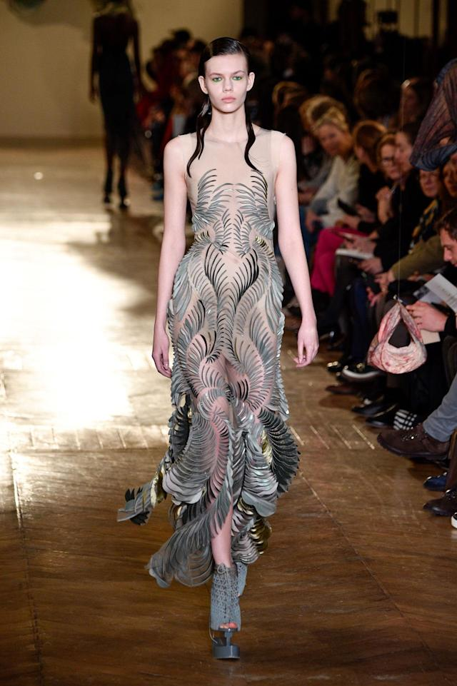 <p>Model wears a semi-sheer dress with silver and gold embellishments from the Iris Van Herpen SS18 Haute Couture show. (Photo: Getty Images) </p>