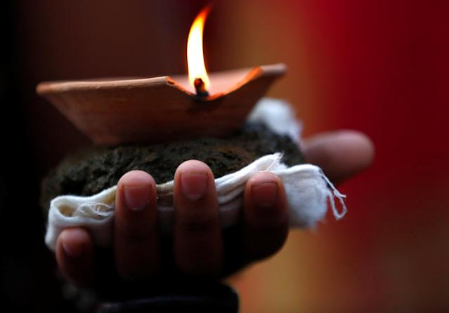 "<p>A lit oil lamp is placed on the hand of a devotee while offering prayers during ""Dashain"", a Hindu religious festival in Bhaktapur, Nepal, Sept. 30, 2017. (Photo: Navesh Chitrakar/Reuters) </p>"