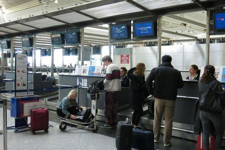 A passenger places her computer in her suitcase before the British Airways check-in desk at Ataturk International airport in Istanbul