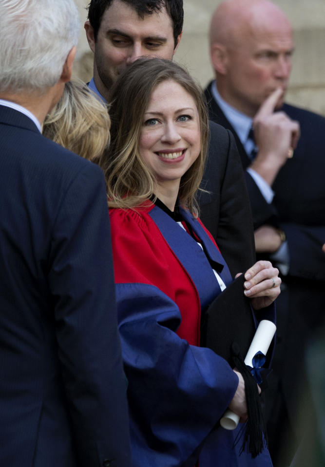 Chelsea Clinton, center, holds her certificate as she waits to pose for a formal photograph with her husband Marc Mezvinsky, center top, and her parents former U.S. President Bill Clinton, left, and former Secretary of State Hillary Rodham Clinton, second left obscured, after they attended Chelsea's Oxford University graduation ceremony at the Sheldonian Theatre in Oxford, England, Saturday, May 10, 2014. Chelsea Clinton received her doctorate degree in international relations on Saturday from the prestigious British university. Her father was a Rhodes scholar at Oxford from 1968 to 1970. The graduation ceremony comes as her mother is considering a potential 2016 presidential campaign. (AP Photo/Matt Dunham)
