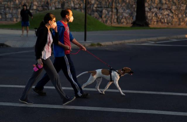 FILE PHOTO: A couple walk their pet before night-time curfew announced by the government to keep people off the streets, to prevent infections amid the coronavirus disease (COVID-19) outbreak, in Vina del Mar