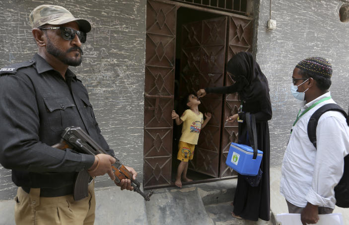 A police officer stands guard while a healthcare worker administers a polio vaccine to a child, in Karachi, Pakistan, Wednesday, June 9, 2021. Gunmen on a motorcycle Wednesday shot and killed two police officers assigned to protect polio vaccination workers in the district of Mardan in Khyber Pakhtunkhwa province, northwest Pakistan before fleeing, police said. (AP Photo/Fareed Khan)