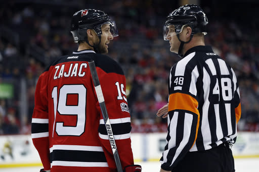File-This March 28, 2017, file photo shows New Jersey Devils center Travis Zajac, left, talking to referee Garrett Rank, right, during the first period of an NHL game, in Newark, N.J. Rank, a full-time NHL referee who played only four rounds of golf during the hockey season, was co-medallist at his qualifying site in Georgia and will play his first U.S. Open this week. Rank, of Elmira, Ont., worked 73 games during the regular season and three playoff games in his second NHL season. But his golf resume is just as impressive. He is a three-time Canadian Mid-Amateur Champion and represented Canada at the Pan-Am Games in 2015. (AP Photo/Julio Cortez, File)