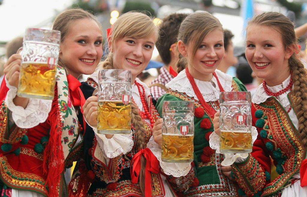 Polish girls dressed in traditional costume enjoy beer after participating in the opening parade.