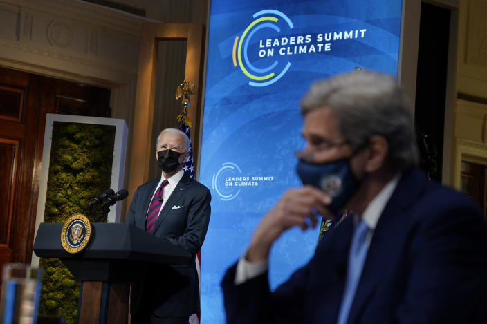 President Joe Biden speaks to the virtual Leaders Summit on Climate, from the East Room of the White House, Thursday, April 22, 2021, in Washington, as Special Presidential Envoy for Climate John Kerry, looks on. (AP Photo/Evan Vucci)