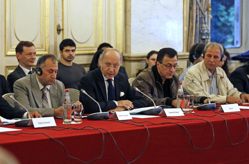 French foreign minister Laurent Fabius, center, delivers his opening speech at the start of a conference gathering representatives of Syrian rebels, at the Quai d'Orsay in Paris, Wednesday Oct. 17, 2012. Delegates of Syrian revolutionary councils are meeting in Paris Wednesday with officials from some 20 countries to plan an expansion of a French initiative of direct aid to beleaguered rebel-held towns in Syria. (AP Photo/Remy de la Mauviniere)