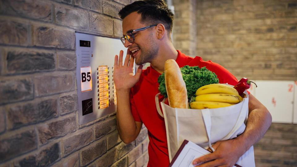 Delivery man informing his customer via intercom that the order has arrived.