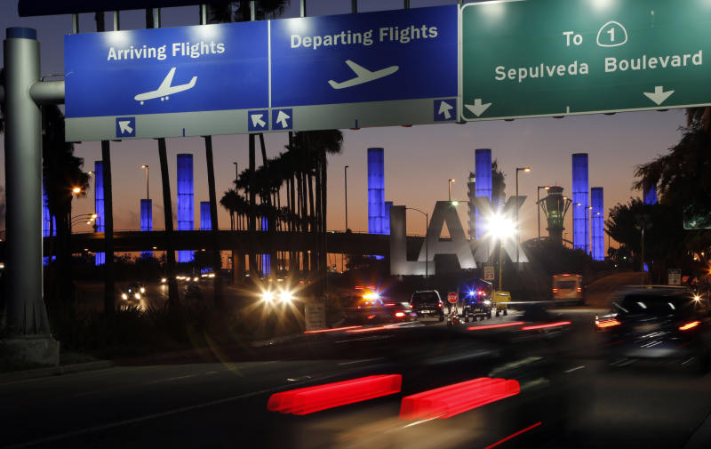 FILE - In this Nov. 2, 2013 file photo lighted pylons line the entrance to Los Angeles International Airport in Los Angeles. At the end of the month, travelers will not be able to hail a rideshare or taxi outside terminals at Los Angeles International Airport. LAX announced Friday, Oct. 4, 2019, that travelers will instead have to take shuttles or walk to a special location outside the central terminal area where they can be picked up. (AP Photo/Reed Saxon,File)