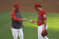 Los Angeles Angels manager Joe Maddon, left, takes starting pitcher Matt Andriese out of the game during the second inning of a baseball game against the Houston Astros Friday, July 31, 2020, in Anaheim, Calif. (AP Photo/Mark J. Terrill)