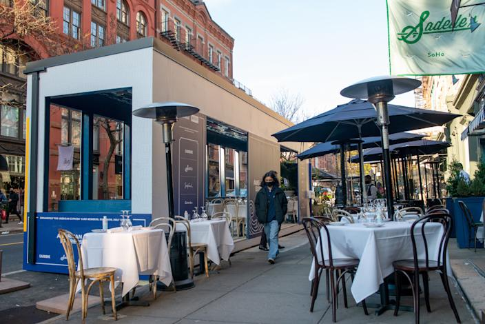 NEW YORK, NEW YORK - NOVEMBER 29: A woman walks by an American Express and Resy-sponsored outdoor dining area at Sadelle's  in SoHo on November 29, 2020 in New York City. The pandemic continues to burden restaurants and bars as businesses struggle to thrive with evolving government restrictions and social distancing plans which impact keeping businesses open yet challenge profitability. (Photo by Alexi Rosenfeld/Getty Images)