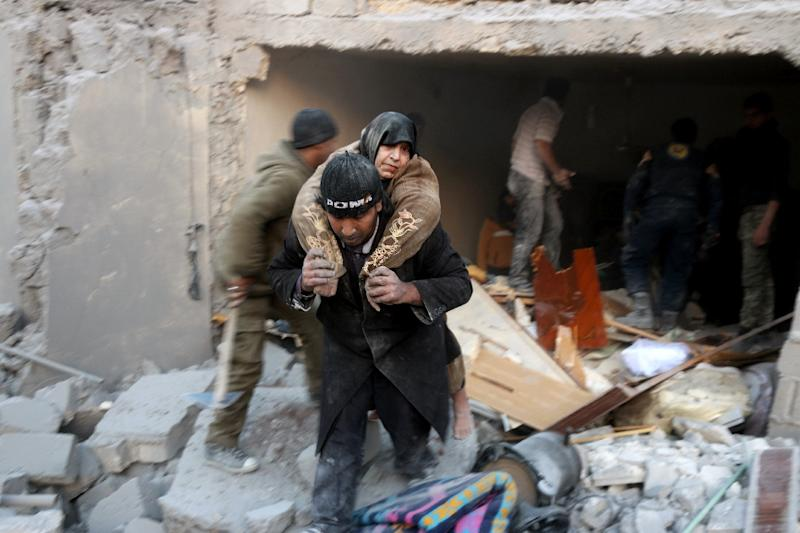 A man carries a woman from the rubble of a building following reported airstrikes on Aleppo's rebel-held district of al-Hamra on November 20, 2016 (AFP Photo/Thaer Mohammed)