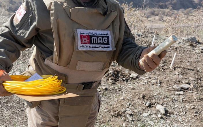 A Mine Advisory Group de-miner holds an explosive with which he will detonate landmines planted during the Iran-Iraq war, near the Iranian border in Iraq - Sam Tarling/Sam Tarling