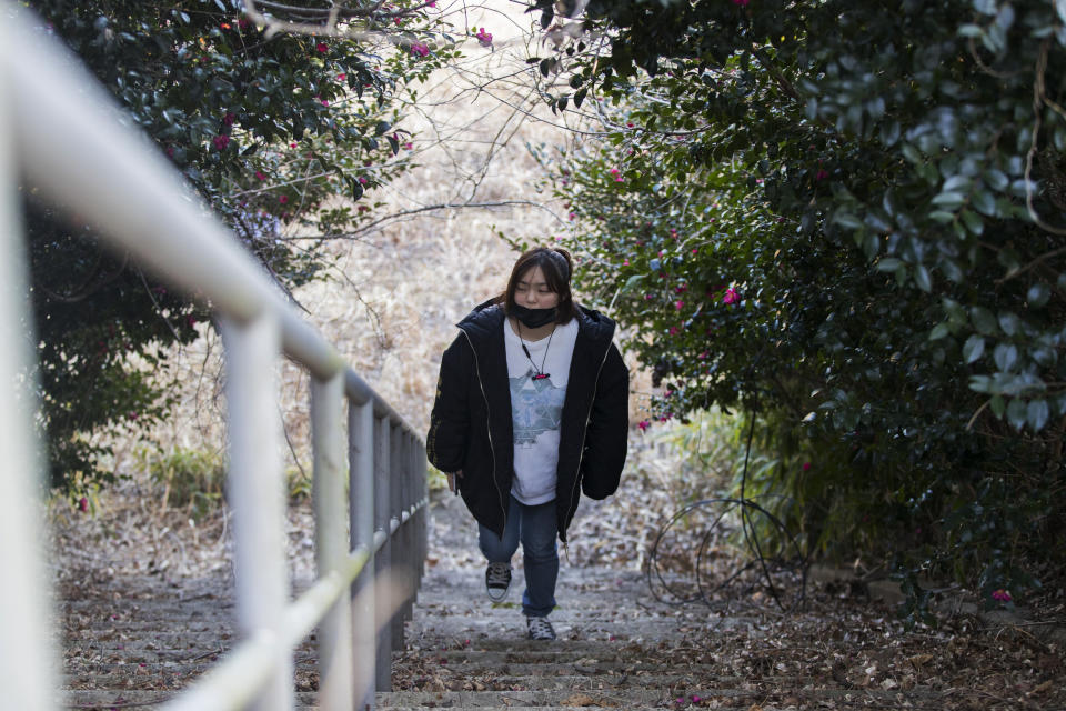 Hazuki Sato, a Futaba town official, walks around an elementary school she used to attend until she evacuated due to a nuclear scare following a 2011 earthquake, during an interview with The Associated Press in Futaba town, Fukushima prefecture, northeastern Japan, Sunday, Feb. 28, 2021. She's now preparing for the coming-of-age ceremony that is typical for Japanese 20-year-olds, hoping for a reunion in town so she can reconnect with her former classmates who have scattered. (AP Photo/Hiro Komae)