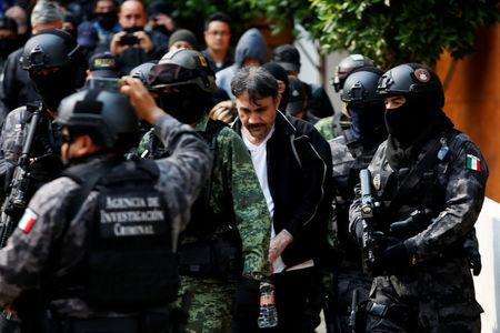 "Accused drug kingpin Damaso Lopez, nicknamed ""The Graduate"", is escorted by police officers after he was arrested in Mexico City"