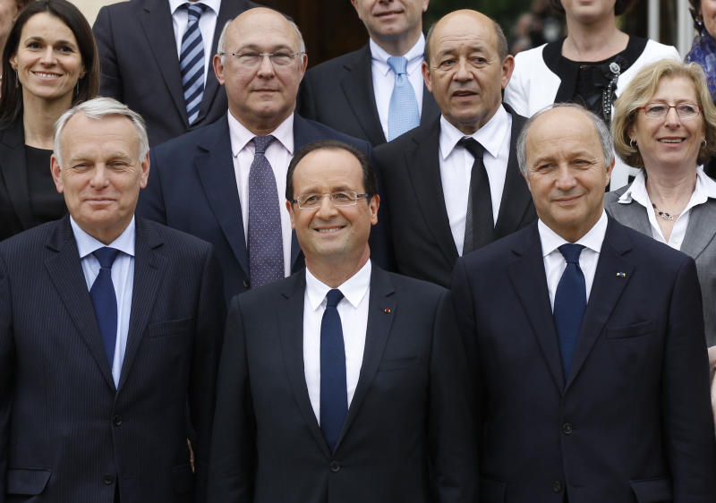 French President Francois Hollande, center, poses with the ministers  after the first weekly cabinet meeting with Thursday, May 17, 2012 at the Elysee Palace in Paris. First row,  from left are: Prime Minister Jean-Luc Ayrault, Foreign Minister Laurent Fabius. Second row from the left are: Culture Minister Aurelie Filippeti, Labor Minister Michel Sapin, Defense Minister Jean-Yves le Drian, and Research Minister Genevieve Fioraso. (AP Photo/Michel Euler)