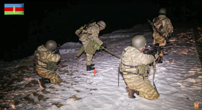 This photo taken from a video released by Azerbaijan's Defense Ministry on Wednesday, Nov. 25, 2020, shows an Azerbaijan's army soldiers and a de-miner during mine clearance in Kalbajar region of Azerbaijan. The Kalbajar district bordering Armenia, which houses one of the two roads linking Nagorno-Karabakh and the neighbouring country and has strategic significance for Armenians and Azeris, is due to be handed over to Azerbaijan according to a Russia-brokered cease-fire agreement between two countries in the long-running conflict over the separatist territory. (Azerbaijan's Defense Ministry via AP)
