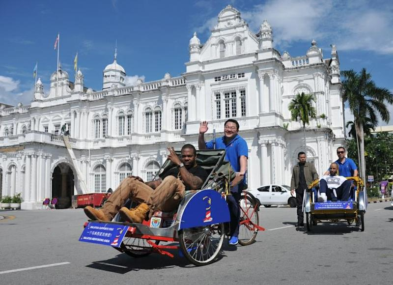 Jho Low (centre) pedals a trishaw carrying US rapper Busta Rhymes in George Town in this file picture taken on April 19, 2013. — Picture by KE Ooi