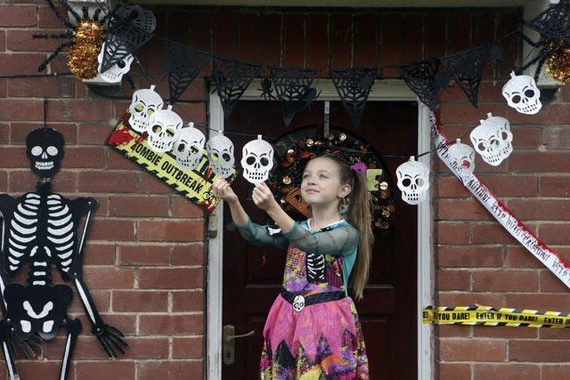 Talulah Hudson, eight, adjusts Halloween decorations outside her home in Woodlesford, Leeds (Danny Lawson/PA)