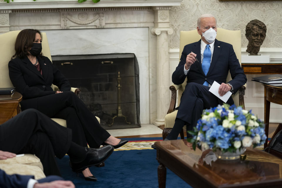 Vice President Kamala Harris listens as President Joe Biden speaks during a meeting with a bipartisan group of mayors and governors to discuss a coronavirus relief package, in the Oval Office of the White House, Friday, Feb. 12, 2021, in Washington. (AP Photo/Evan Vucci)