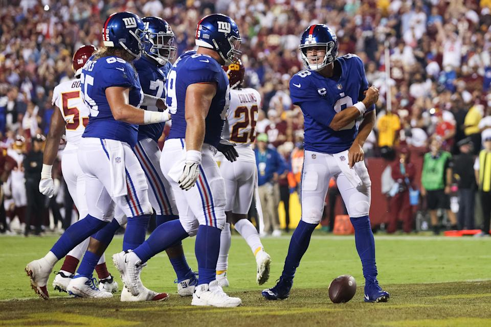 Daniel Jones of the New York Giants celebrates with teammates after rushing for a touchdown during the first quarter against the Washington Football Team at FedExField on September 16, 2021 in Landover, Maryland.