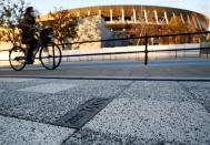 FILE PHOTO: A woman cycles past a sign for Tokyo 2020 Olympic Games on the pavement in front of the National Stadium, the main stadium of Tokyo 2020 Olympics and Paralympics, in Tokyo