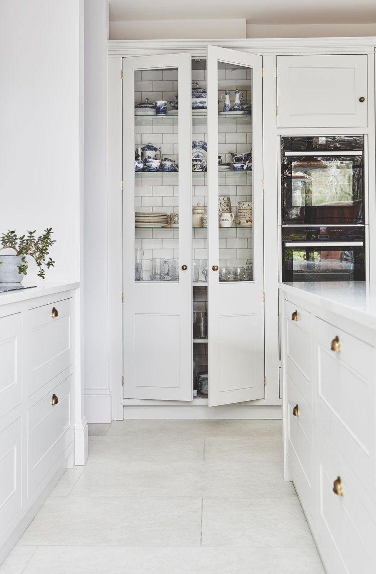 """<p>Not an inch is overlooked in this bespoke white kitchen by Blakes London. White kitchen tiles add texture and a touch of the unexpected in this display cabinet, as well as being a fitting backdrop to patterned crockery and glassware.</p><p>Pictured: <a href=""""https://www.blakeslondon.com/wandsworth/"""" rel=""""nofollow noopener"""" target=""""_blank"""" data-ylk=""""slk:Kitchen by Blakes London"""" class=""""link rapid-noclick-resp"""">Kitchen by Blakes London</a></p>"""