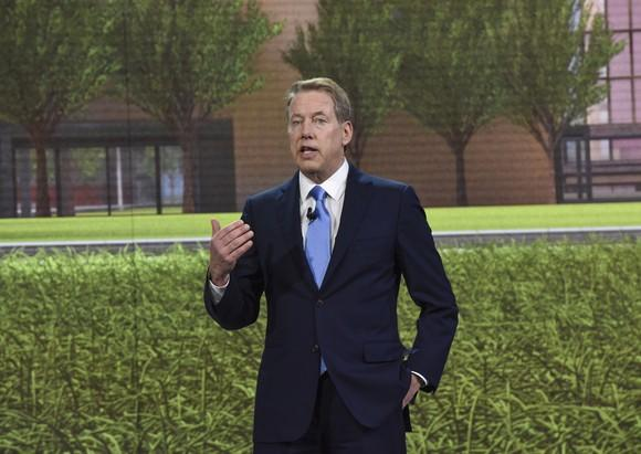 Bill Ford is shown speaking onstage, before an image of a green lawn in front of a brick building.