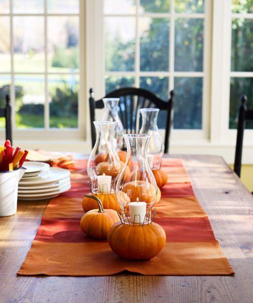 <p>One way to cast glimmering candlelight across the entire table? Top pumpkins with votives and shield the flames by securing glass hurricanes with floral U-pins.</p>