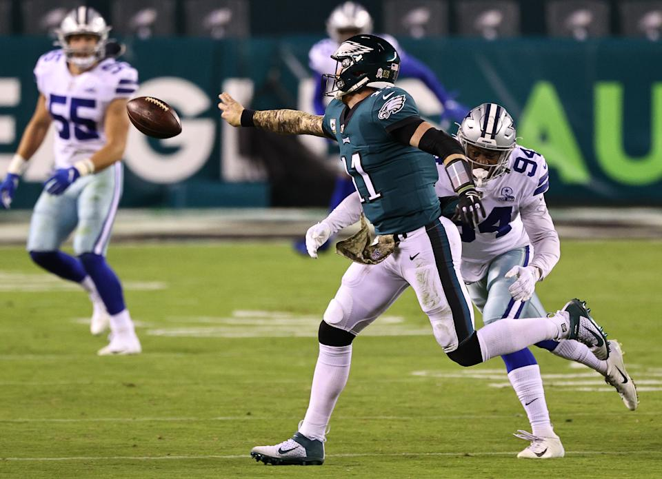 Quarterback Carson Wentz #11 of the Philadelphia Eagles flicks an incomplete pass while under pressure from Randy Gregory #94 of the Dallas Cowboys in the third quarter of the game at Lincoln Financial Field on November 01, 2020 in Philadelphia, Pennsylvania. (Photo by Elsa/Getty Images)