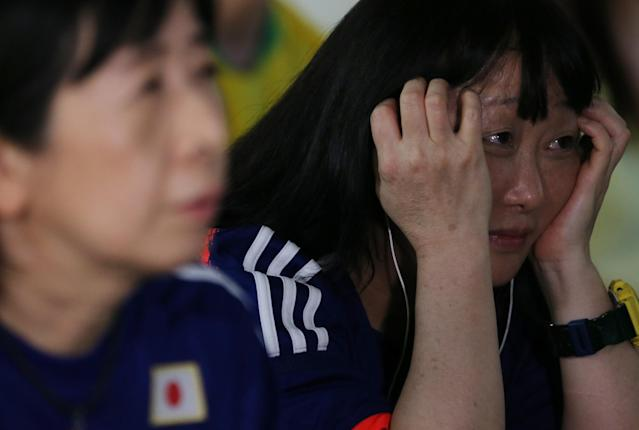 <p>Japanese descendants react during the broadcast of the FIFA World Cup soccer match. REUTERS/Paulo Whitaker </p>