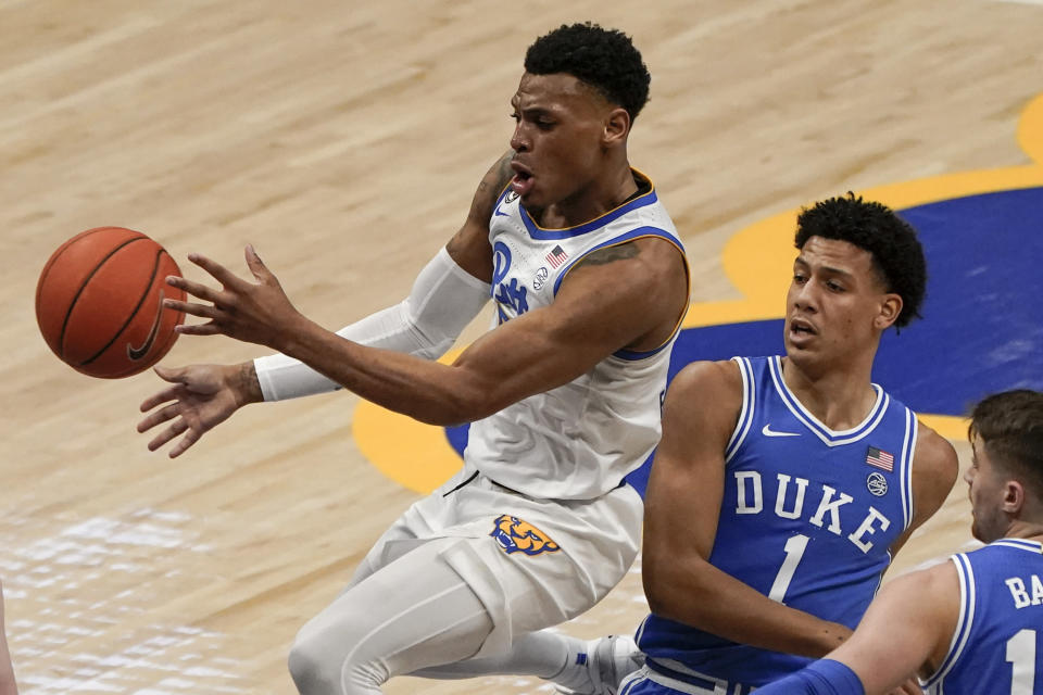 Pittsburgh's Au'diese Toney, left, passes after getting by Duke's Jalen Johnson (1) during the first half of an NCAA college basketball game, Tuesday, Jan. 19, 2021, in Pittsburgh. (AP Photo/Keith Srakocic)