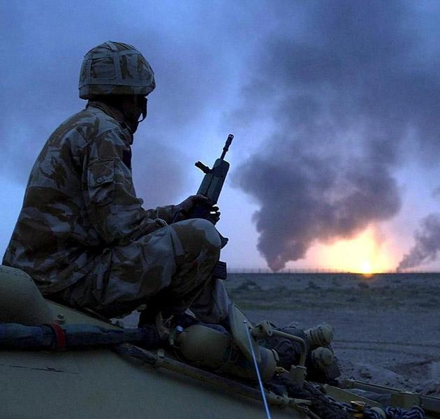 A photo released on March 23, 2003 shows a British soldier watching burning oil wells in southern Iraq on March 20.  The US-led invasion of Iraq that toppled Saddam Hussein sought to enshrine a liberal democracy in the heart of the Middle East but instead unleashed brutal sectarian violence and endless political disputes.