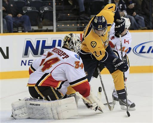 Calgary Flames goalie Miikka Kiprusoff (34), of Finland, blocks a shot as Nashville Predators right wing Patric Hornqvist (27), of Sweden, watches for the rebound in the second period of an NHL hockey game on Tuesday, Dec. 13, 2011, in Nashville, Tenn. (AP Photo/Mark Humphrey)