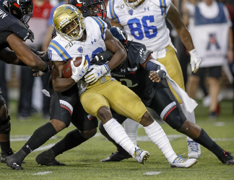 UCLA's Demetric Felton is tackled by Cincinnati's Jarell White during the Bearcats' win on Thursday. (Getty)