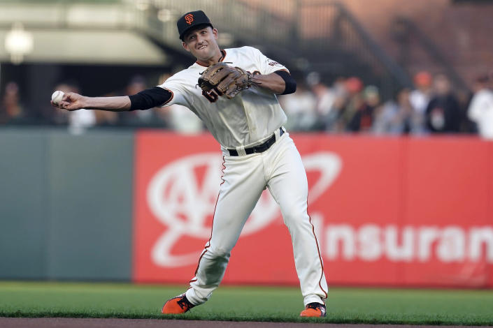 San Francisco Giants' Jason Vosler throws out Milwaukee Brewers' Kolten Wong at first base during the first inning of a baseball game in San Francisco, Monday, Aug. 30, 2021. (AP Photo/Jeff Chiu)