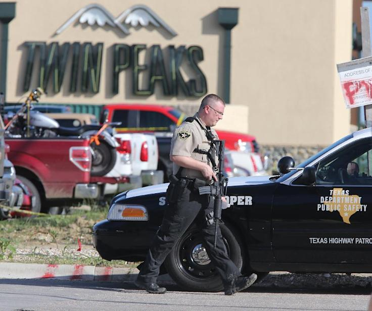 An officer secures the scene Sunday outside a Twin Peaks restaurant where a shootout left nine people dead in Waco, Texas. (Jerry Larson/AP)