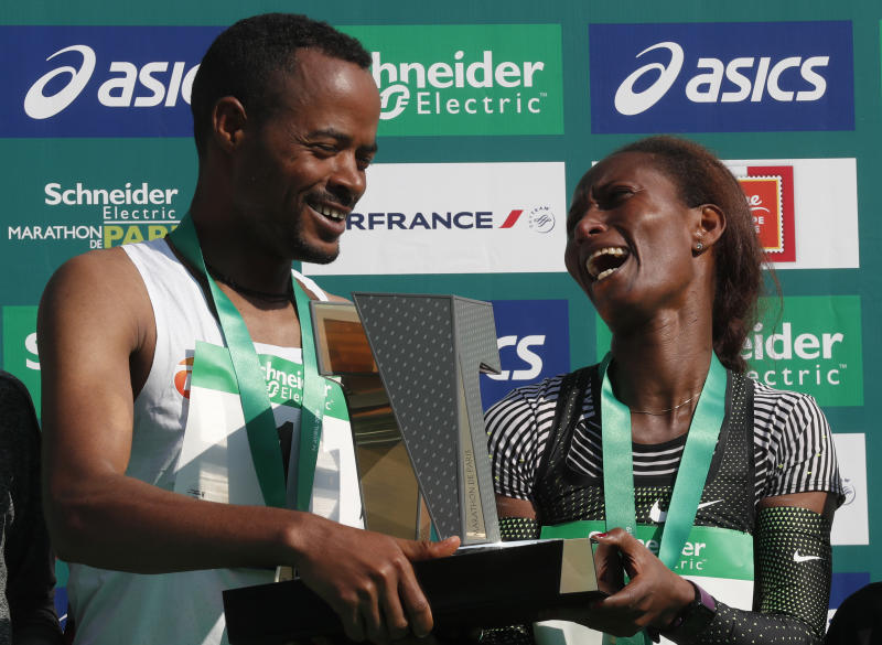 Abrha Milaw of Ethiopia, left, winner of the men's Paris Marathon with Gelete Burka of Ethiopia who won the women's race smile as they stand on the winners podium following the race in Paris, France, Sunday, April 14, 2019. (AP Photo/Thibault Camus)