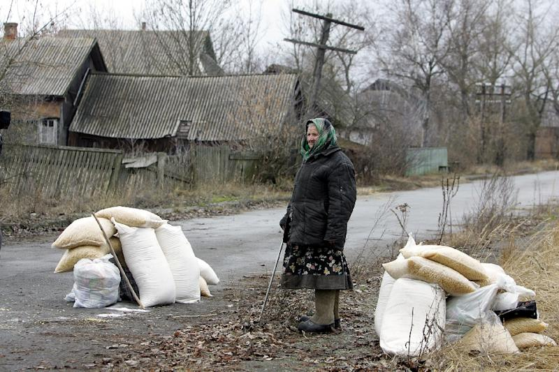 "A ""samosely"" (self-returner), as illegal inhabitants of the exclusion zone around the Chernobyl nuclear power plant are known, stands next to bags of flour and macaroni given by Ukraine Emergencies Ministry personnel"
