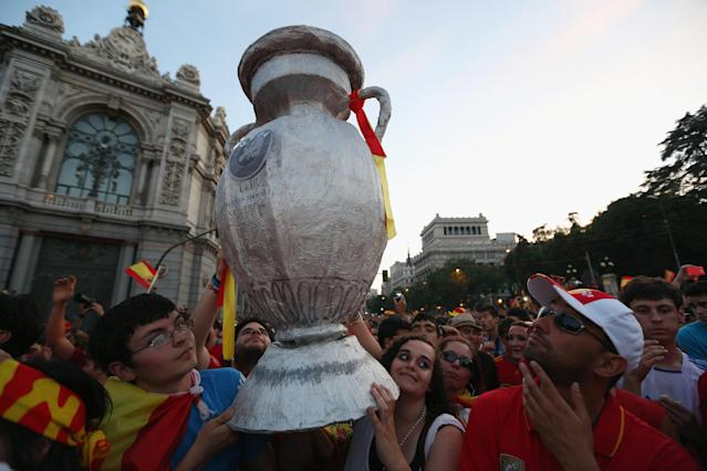 MADRID, SPAIN - JULY 02: Supporters of Spain's national football team hold a home-made replica trophy aloft to congratulate their team's players as they return to Madrid following their victory in the UEFA EURO 2012 football championships on July 2, 2012 in Madrid, Spain. Spain beat Italy 4-0 in the UEFA EURO 2012 final match in Kiev, Ukraine, on July 1, 2012. (Photo by Oli Scarff/Getty Images)