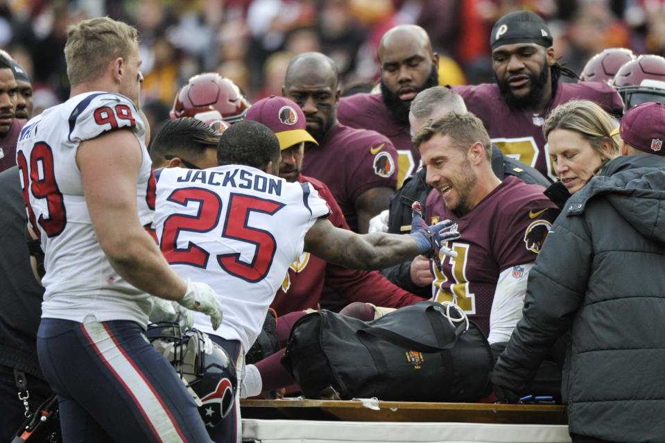 Texans safety Kareem Jackson (25) reaches out in support of Redskins quarterback Alex Smith (11) as he leaves the field after a devastating injury on Nov. 18, 2018. (AP Photo/Mark Tenally)