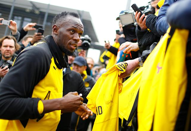 Soccer Football - Usain Bolt participates in a training session with Borussia Dortmund - Strobelallee Training Centre, Dortmund, Germany - March 23, 2018 Usain Bolt signs autographs for fans after Borussia Dortmund training REUTERS/Thilo Schmuelgen