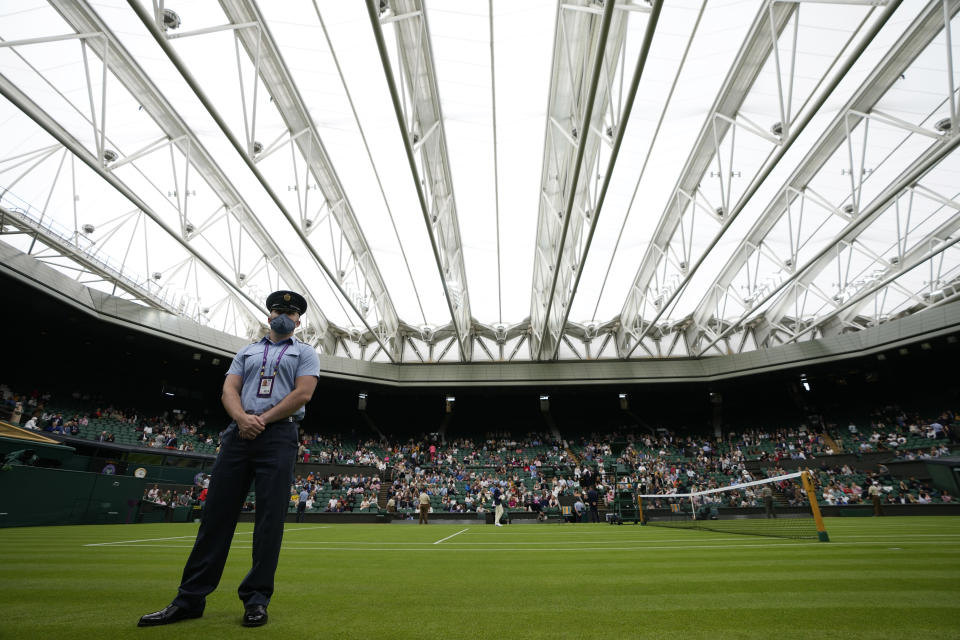 A steward stands on Centre Court covered with the roof ahead of the men's singles match between Serbia's Novak Djokovic and Britain's Jack Draper on day one of the Wimbledon Tennis Championships in London, Monday June 28, 2021. (AP Photo/Kirsty Wigglesworth)