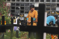 A woman wearing face mask as a precaution against the coronavirus prays at the grave of a deceased relative during All Souls Day in Mumbai, India, Monday, Nov. 2, 2020. (AP Photo/Rafiq Maqbool)