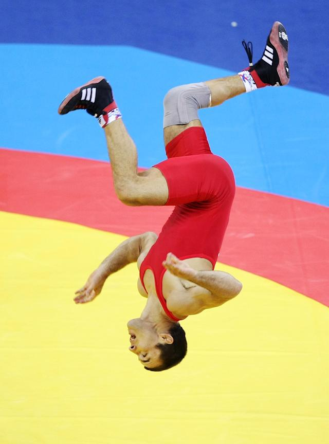 BEIJING - AUGUST 19: Radoslav Velikov of Bulgaria celebrates by doing a flip after defeating Namig Sevdimov of Azerbaijan in the bronze medal bout during the men's 55kg freestyle wrestling event at the China Agriculture University Gymnasium on Day 11 of the Beijing 2008 Olympic Games on August 19, 2008 in Beijing, China. (Photo by Jed Jacobsohn/Getty Images)