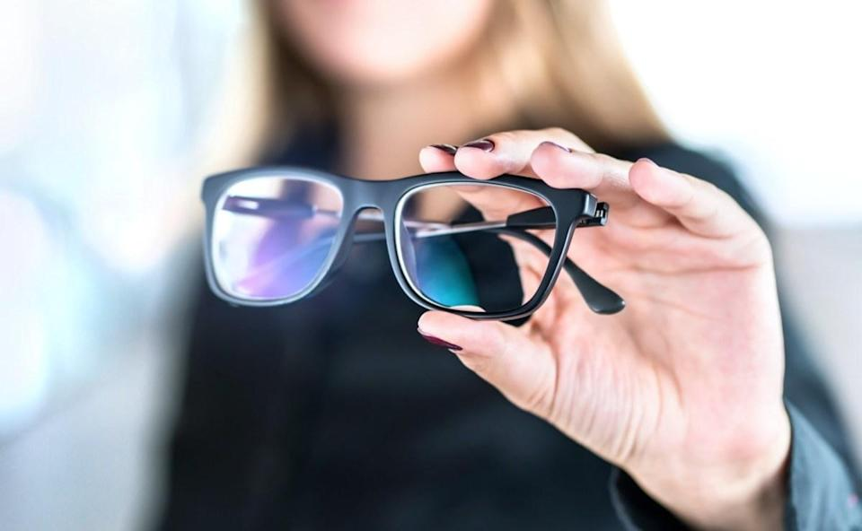 Optician, optometrist, oculist or eye doctor holding glasses and specs with new lenses