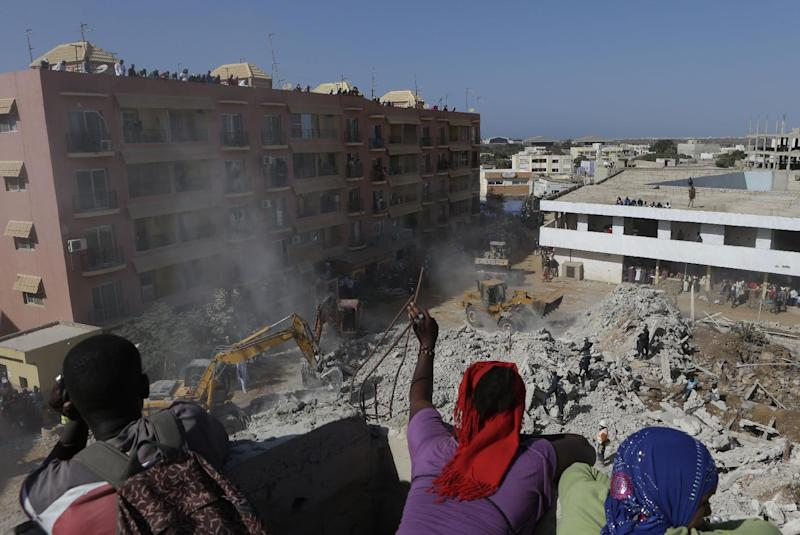 People watch from the rooftop of an adjacent building under construction, as workers clear rubble from the site of a four-storey building that collapsed during construction, in a neighborhood full of buildings under construction, in Dakar, Senegal, Friday, March 8, 2013. Omar Samb Gueye, the local chief of the Ouakam area where the building was being constructed, said two people were killed and two injured when the building folded in on itself and collapsed in Senegal's capital, Dakar. He said the building was being constructed twice as tall as the two-storey height for which it had been authorized. (AP Photo/Rebecca Blackwell)