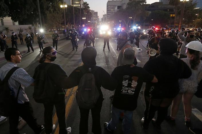 "Protesters link arms during a demonstration Saturday in downtown Los Angeles. <span class=""copyright"">(Luis Sinco / Los Angeles Times)</span>"