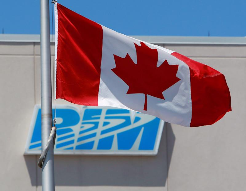 FILE- In this  June 29, 2012, photo, the Canadian Flag flies in front of the Research In Motion (RIM) company logo on one of their many buildings,in Waterloo, Canada. Shareholders of Research In Motion, perhaps some of the most staunch supporters of the BlackBerry smartphone, are expected to take a far more critical view of the embattled company at its annual meeting on Tuesday. (AP Photo/The Canadian Press, Dave Chidley)
