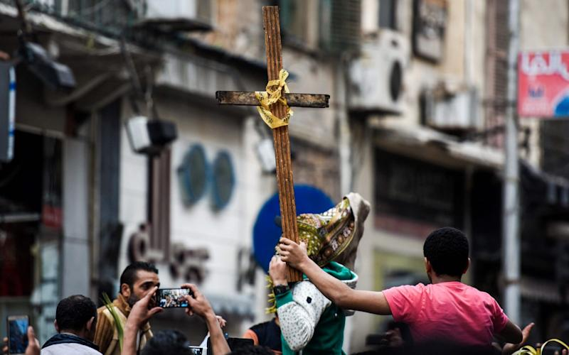 Egyptians raise a wooden cross and palm leaves originally intended for Palm Sunday celebrations, as they gather outside the Coptic Orthodox Patriarchate in Alexandria after a bomb blast struck worshippers gathering to celebrate Palm Sunday on April 9, 2017. - Credit: MOHAMED EL-SHAHED